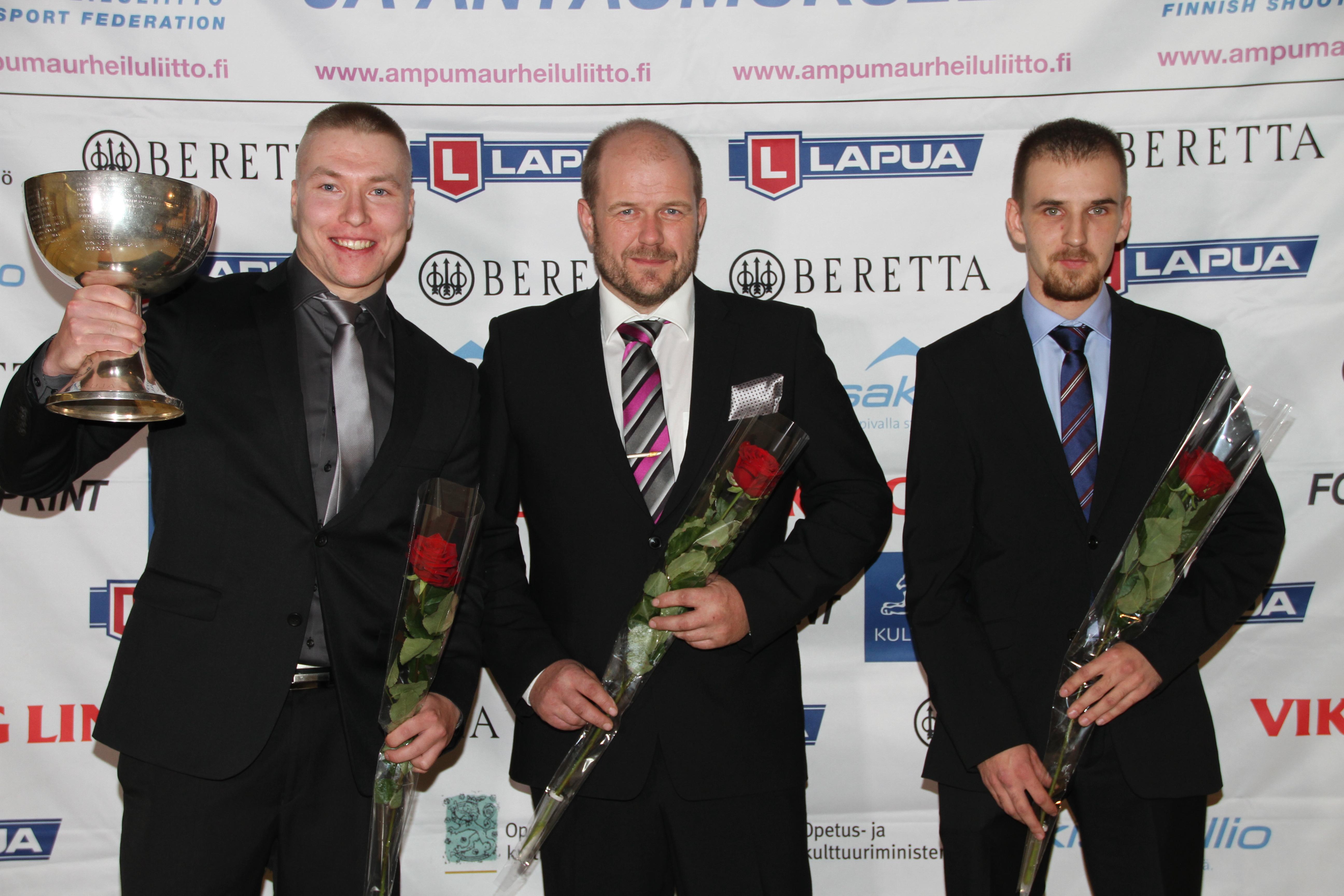 Tomi-Pekka Heikkilä (vas.), Krister Holmberg ja Heikki Lähdekorpi ja Vuoden ampumaurheilija -pokaali. (Kuvat; Lassi Palo)
